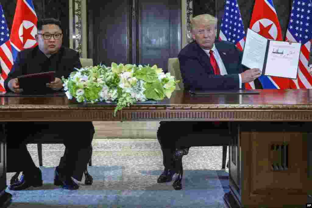 12일 싱가포르 카펠라 호텔에서 도널드 트럼프 미국 대통령이 김정은 북한 국무위원장과 정상회담 공동합의문에 서명한 후 합의문을 들어보이고 있다.