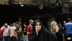 伊拉克妇女等待在自杀式卡车爆炸袭击中失联的亲人。