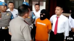 Tersangka DRP (48 tahun, memakai baju tahanan) ditunjukkan kepada wartawan di Mapolrestabes Bandung, Senin (21/1/2019) siang. (VOA/Rio Tuasikal)
