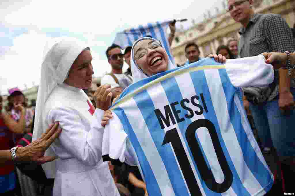 A nun holding an Argentine national soccer team jersey with the number of player Lionel Messi, smiles as she waits for Pope Francis' Sunday Angelus prayer in Saint Peter's square at the Vatican.