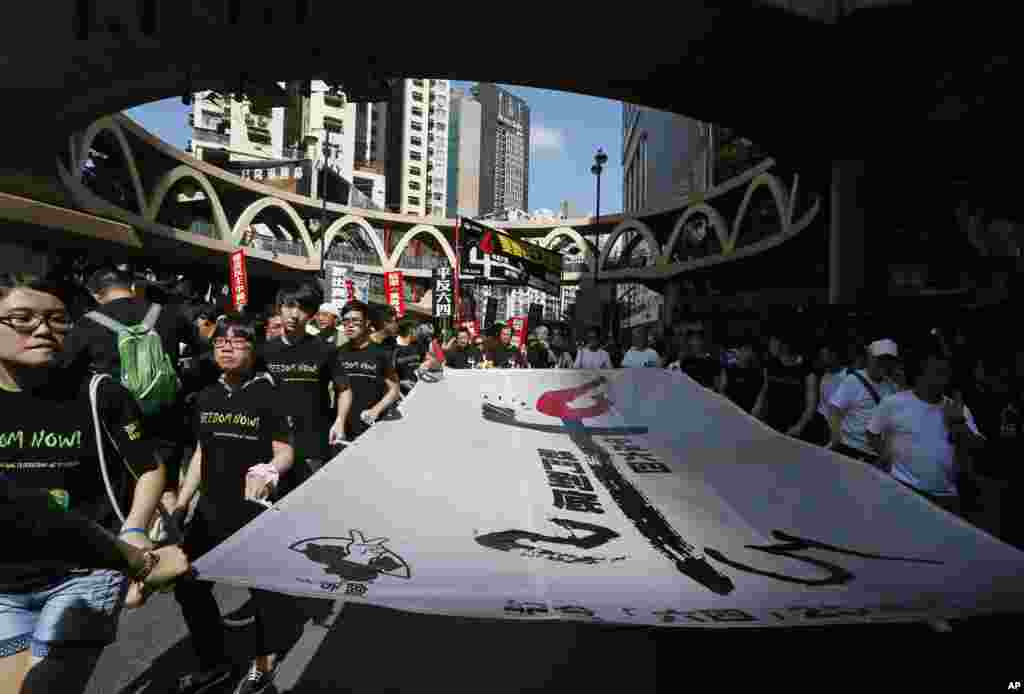 "Protesters carry a huge banner with Chinese words ""Exonerate the June 4 Protest"" as thousands of people march on a downtown street in Hong Kong to mark the 25th anniversary of China's bloody crackdown on Tiananmen Square on June 4, 1989."