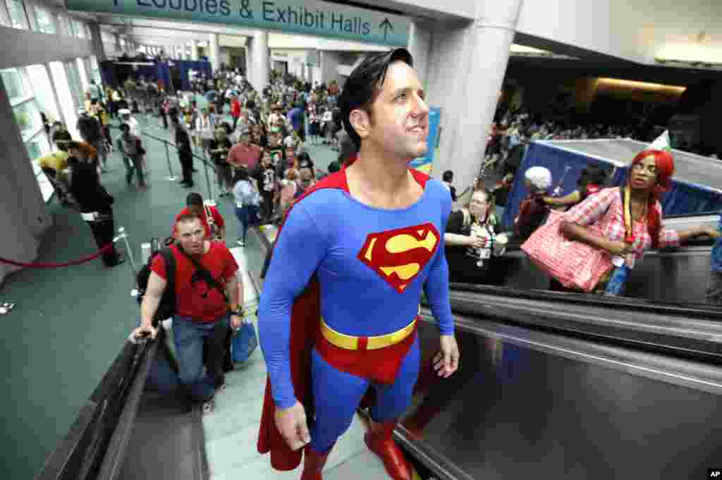 Trey Moore, dressed as Superman, rides the escalator on first day of Comic-Con convention held at the San Diego Convention Center, July 12, 2012, in San Diego.