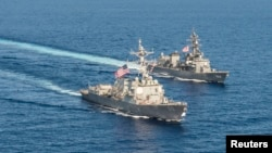 Le destroyer de missiles guidés de classe Arleigh Burke USS Mustin (DDG 89) avec le navire JS Kirisame (DD 104) du Japan Maritime Self-Defense Force lors d'un entrainement conjoint en mer de Chine méridionale le 21 avril 2015.