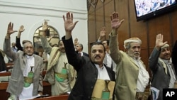 Members of Yemen's parliament raise their hands as they vote in favor of the state of emergency, March 23, 2011, declared by the country's President Ali Abdullah Saleh last week, in Sana'a