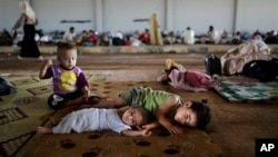 FILE - Syrian refugee children rest at a camp near the Turkish border.
