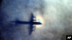 FILE - In this March 31, 2014 file photo, the shadow of a Royal New Zealand Air Force P3 Orion is seen on low level cloud while the aircraft searches for missing Malaysia Airlines Flight MH370 in the southern Indian Ocean, near the coast of Western Australia.