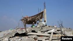 Trẻ em Palestine ngồi trên đống đổ nát của các tòa nhà bị phá hủy trong các vụ không kích của Israel ở Dải Gaza, ngày 13/8/2014.