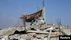 8月13日一群巴勒斯坦儿童坐在他们住房的废墟上