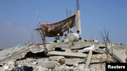 Anak-anak Palestina duduk di atas reruntuhan rumahnya yang hancur akibat serangan Israel di Khan Younis, Jalur Gaza (13/8).