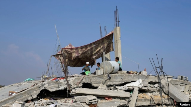 FILE - Palestinian children sit atop the remains of their house, which witnesses said was destroyed in the Israeli offensive, during a 72-hour truce in Khan Younis, southern Gaza Strip.