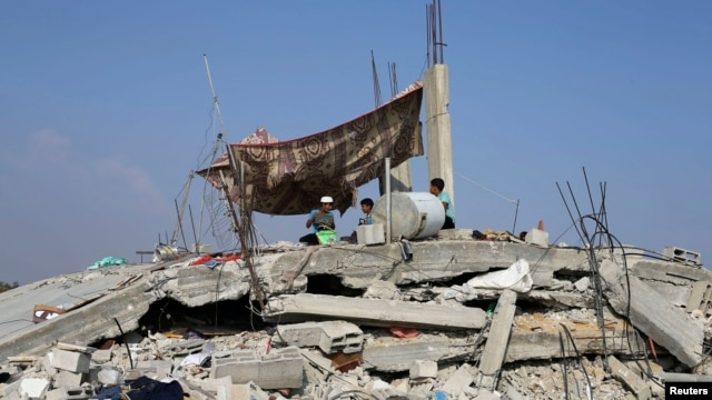 Palestinian children sit atop the remains of their house, which witnesses said was destroyed in the Israeli offensive, during a 72-hour truce in Khan Younis, southern Gaza Strip, Aug. 13, 2014.