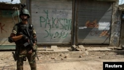 FILE - A Pakistani soldier stands in front of closed shops during a military operation against Taliban militants in the town of Miranshah in North Waziristan, July 9, 2014.