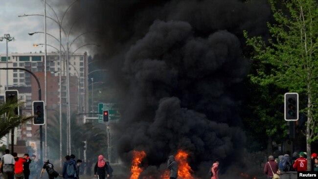 Manifestantes enmascarados junto a una barricada incendiada en Santiago de Chile el 20 de octubre de 2019.