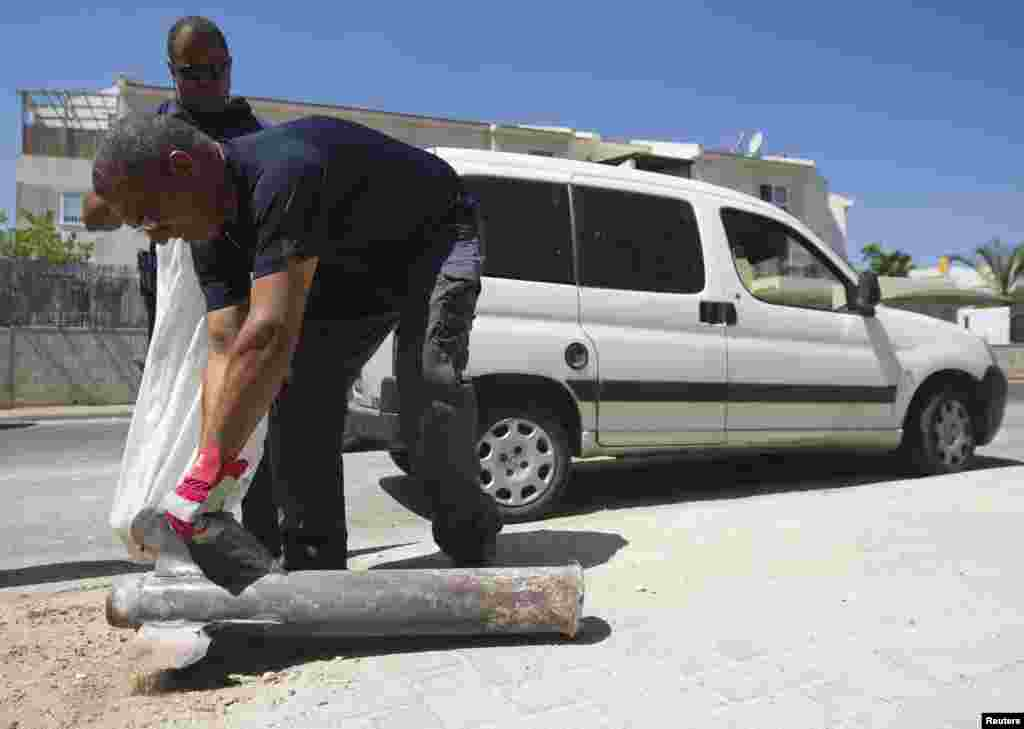 An Israeli police explosives expert displays for the media the remains of a neutralised rocket fired by Palestinian militants in Gaza after it landed in a house in the southern town of Sderot, July 3, 2014.