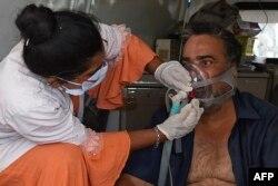 Seorang pasien COVID-19 dengan bantuan oksigen ditolong oleh petugas kesehatan di dalam ambulans sambil menunggu masuk di rumah sakit sipil di Ahmedabad, 3 Mei 2021. (Foto: Sam PANTHAKY / AFP)