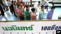 Voters wait in line to cast their votes, next to a board showing information on candidates, at a polling station in Bangkok July 3, 2011.