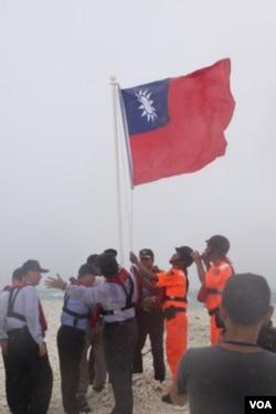 台国安会秘书长胡为真等高官视察南沙群岛,登上太平岛外的中洲礁升旗宣示主权 (台湾国安会提供图片)