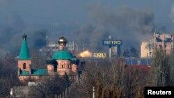 Asap tampak di terminal tua, kiri, dan sebuah gedung di bandara setelah tembakan artileri dalam pertempuran antara separatis pro-Rusia dan pemerintah Ukraina di Donetsk, Ukraina timur, Minggu (9/11).