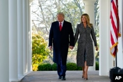 President Donald Trump and first lady Melania Trump walk out of the Oval Office and towards the Rose Garden of the White House, Tuesday, Nov. 24, 2020, in Washington, to pardon Corn, the national Thanksgiving turkey. (AP Photo/Susan Walsh)