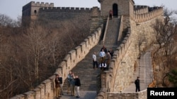 Visitors walk near a section of the Great Wall of China.