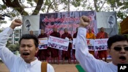 Para pendeta Buddha Myanmar memegang spanduk sementara para demonstran berunjuk rasa di Rangoon, Myanmar (29/12). Mereka meneriakkan protes dan menuntut pembebasan dua pekerja migran yang dijatuhi hukuman mati di Thailand.
