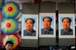 ແມ່ຄ້າຜູ້ນຶ່ງນັ່ງຢູ່ຂ້າງໆຮູບຂອງປະທານ Mao Zedong ທີ່ຈະຕຸລັດ Tiananmen, ປັກກິ່ງ, 9 ກັນຍາ 2016.