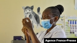 A health worker prepares a malaria vaccination for a child in Yala, Kenya, on Oct. 7, 2021.
