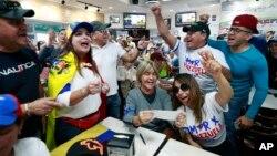 Venezolanos gritaban Viva Venezuela mientras miraban en televisión las noticias de su país en el restaurante venezolano El Arepazo en Doral, Florida, el martes, 30 de abril de 2019.
