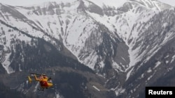 A rescue helicopter from the French Securite Civile flies towards the French Alps during a rescue operation near the crash site of an Airbus A320, near Seyne-les-Alpes, March 24, 2015.