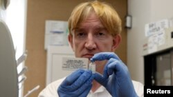 FILE - Professor Adrian Hill, director of Oxford University's Jenner Institute and chief trial researcher, is seen holding a vile with Ebola vaccine.