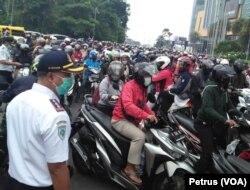 Kepadatan lalu lintas terutama roda dua di bundaran Waru, pintu keluar masuk utama Surabaya dan Sidoarjo saat hari pertama penerapan PSBB (foto: VOA/ Petrus Riski).