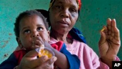 HIV positive child, Gift is given some jam prior to her ARV medication by a carer Tuesday Nov. 30, 2010 near Durban South Africa. (AP Photo/John Robinson)