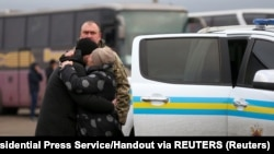 A Ukrainian citizen embraces a relative after the exchange of prisoners of war between Ukraine and the separatist republics near the Mayorsk crossing point in Donetsk region