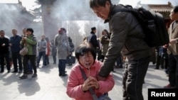 FILE - A crying woman falls on her knees as relatives of passengers onboard of Malaysia Airlines flight MH370 which went missing in 2014, burn incense sticks and pray at Lama Temple in Beijing, China, March 8, 2016.
