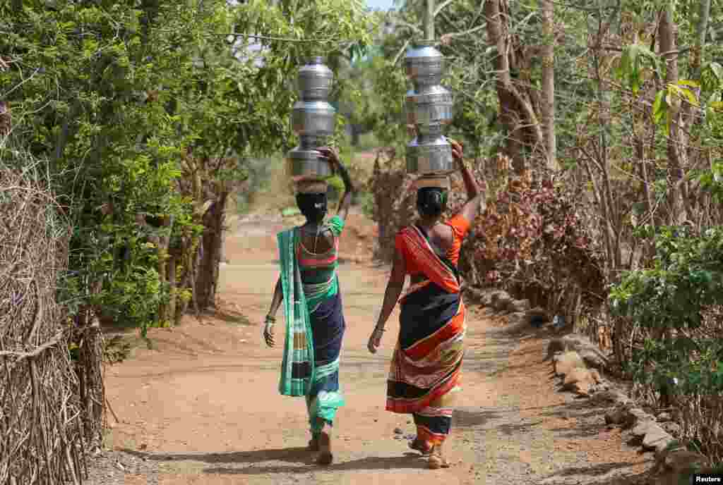 Women carry water pitchers to their houses in Thane district in the western state of Maharashtra, India.