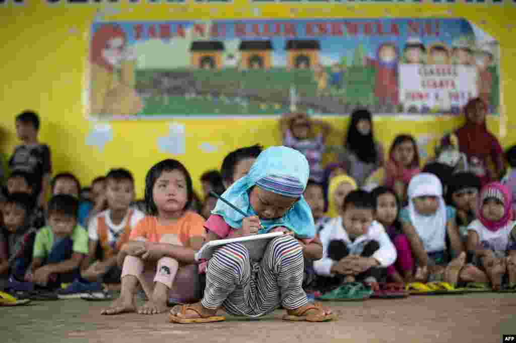Johainah Nasrodeng, 5, writes in her notebook at a makeshift classroom at the Pantar Central Elementary School in Pantar, Lanao del Norte on the southern island of Mindanao, Philippines.  The schoolchildren, some 238 of them with their parents fled by foot for eight hours from Marawi City to Pantar municipality to escape heavy fighting between the government troops and Islamists militants.