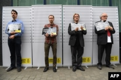 FILE - Former and current heads of Amnesty International in Belgium, (L-R) Vincent Forest, Francois Graas, Rik Vereecken and Willy Laes, stage a mock arrest in front of the Turkish embassy to protest against the detention of Taner Kilic, head of Amnesty I