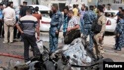 Warga berkumpul di lokasi serangan bom di kota Basra, sekitar 420 km sebelah tenggara Baghdad hari Minggu (16/6).