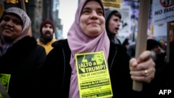 FILE - A Muslim woman holds a poster during a protest against Donald Trump in New York, Dec. 20, 2015.