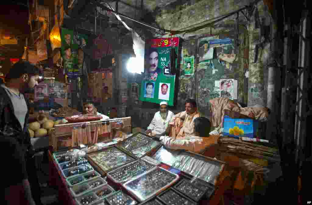 A vendor talks to a customer as others chat at a stall next to posters of various candidates for the upcoming election pasted on a wall in Rawalpindi, Pakistan, May 8, 2013.