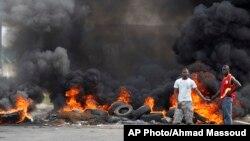 Deux jeunes ivoiriens se tiennent devant une barricade en feu érigée dans le quartier de Koumassi à Abidjan lors des affrontements entre les partisans du candidat de l'opposition Alassane Ouattara et ceux du président sortant Laurent Gbagbo qui refusent de céder le pouvoir, Abidjan, Côte d'Ivoire, 6 décembre 2010.