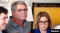 Pascal Fauret (C), one of the two French pilots who had been in the Dominican Republic awaiting a court appeal of their conviction for drug trafficking and now back in France, attends a news conference with his wife Sabine Fauret (R) at his lawyer's office in Paris, Oct. 27, 2015.