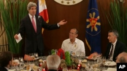 Menlu AS John Kerry (berdiri) memberikan pidato, sebelum acara makan malam dengan Presiden Filipina Benigno Aquino dan Menlu Albert del Rosario di Manila hari Selasa (17/12).
