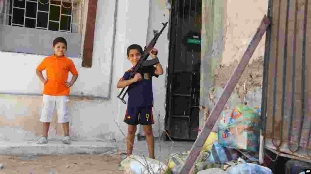 A Libyan child plays with a gun of the local militia. It is not loaded, Tripoli, August 27, 2011 (VOA - E. Arrott)