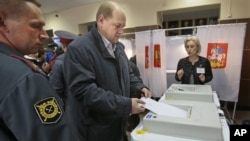 A man casts his ballot paper at a polling station in the town of Khimki outside Moscow, Russia, October 14, 2012.