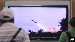 FILE - People watch a TV news program showing the missile launch conducted by North Korea, at Seoul Railway Station in Seoul, South Korea, June 29, 2014.