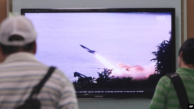 People watch a TV news program showing the missile launch conducted by North Korea, at Seoul Railway Station in Seoul, South Korea, June 29, 2014.