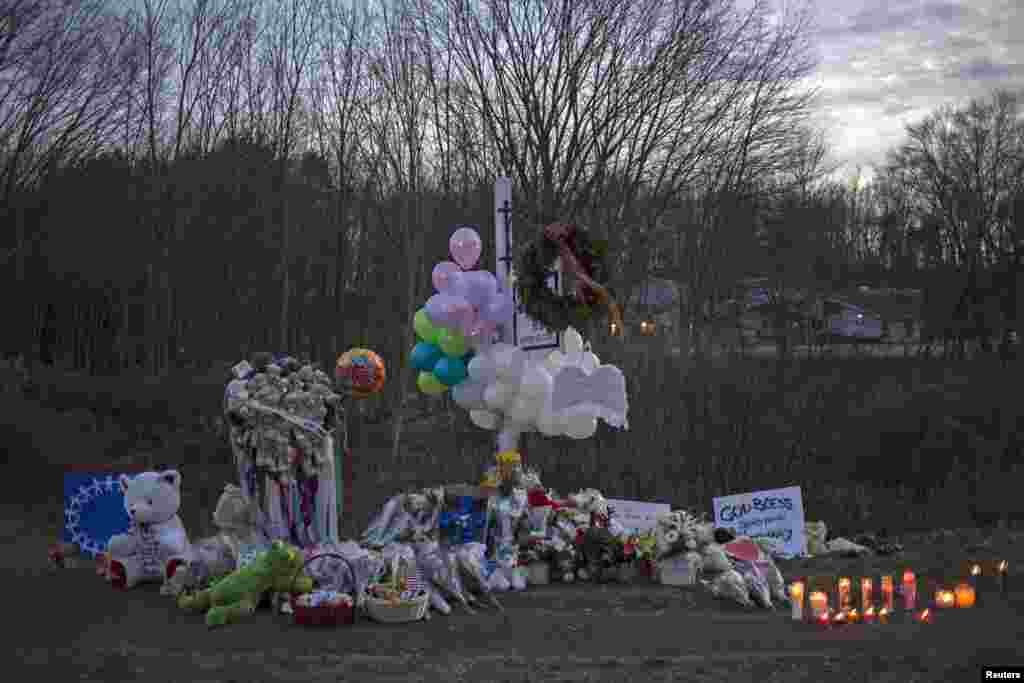 A memorial is seen along the road to Sandy Hook Elementary School a day after a mass shooting in Newtown, Connecticut, December 15, 2012.