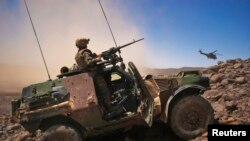 A French soldier stands guard in an armoured vehicle in the Terz valley, about 60 km (37 miles) south of the town of Tessalit in northern Mali March 21, 2013.