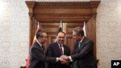 Afghanistan's Minister of Foreign Affairs Salahuddin Rabbani, center, Pakistan's Foreign Minister Shah Mehmood Qureshi, first right, and Chinese Foreign Minister Wang Yi, first left, shake hands after signing the agreement at the presidential palace in Kabul, Dec. 15, 2018.